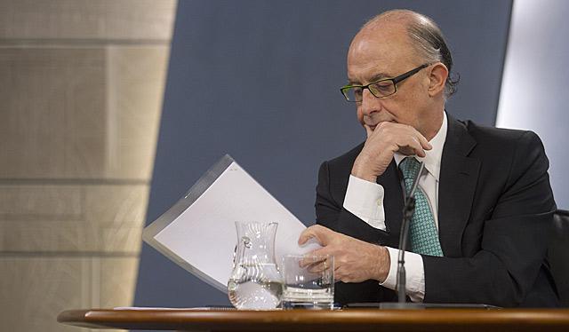 El ministro de Hacienda, Cristóbal Montoro, ojea uno de sus papeles.   Alberto Cuéllar