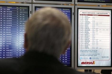 Panel en el aeropuerto de Barajas con los vuelos cancelados este lunes.   Efe