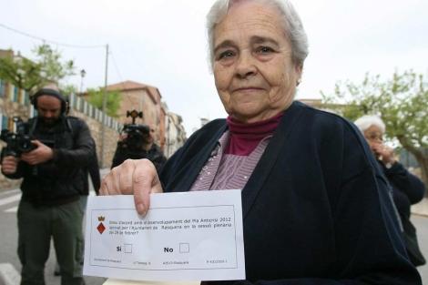 Una vecina muestra su papeleta antes de acudir a votar. | Efe