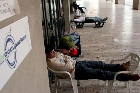 Desempleados italianos duermen a la entrada de una oficina de empleo en Calabria. | Efe