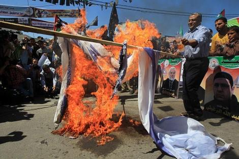 Manifestantes palestinos queman una bandera de Israel en Gaza. | AFP