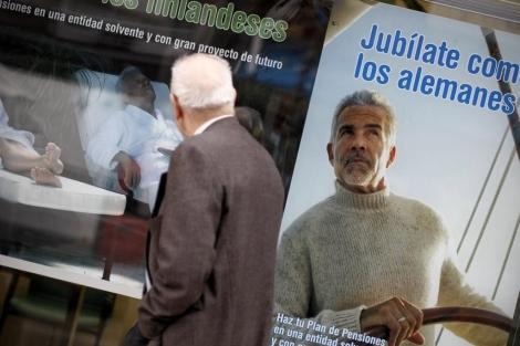 Un anciando mira un cartel que anuncia un producto financiero para mayores.   Alberto Di Lolli