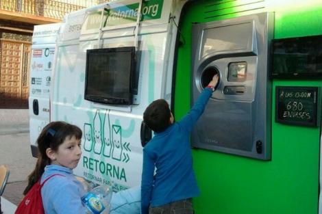 Unos niños devuelven envases en las máquinas experimentales. | Retorna