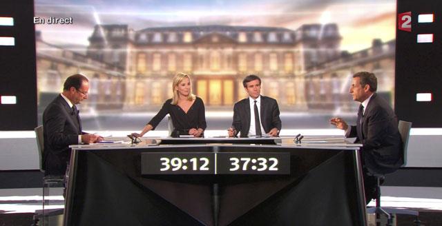 François Hollande (izqda.) y Nicolas Sarkozy, junto a los moderadores durante el debate. | Reuters