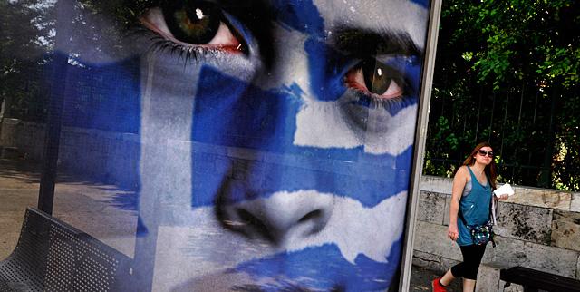 Una mujer, ante un cartel electoral del en Atenas.   AFP