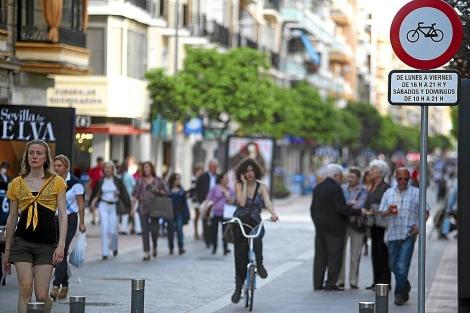 Una joven en bicicleta transita por la calle Asunción entre peatones. | Conchitina