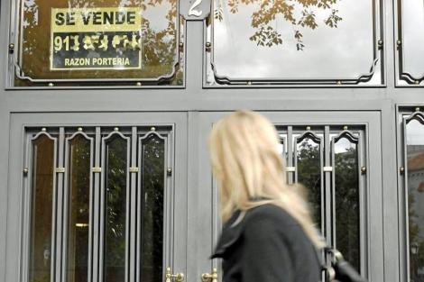 Una chica mira hacia un cartel de 'Se vende' en Madrid. | Bernardo Díaz