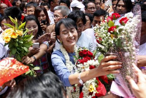Aung San Suu Kyi, recibida con flores a su paso por Rangún el pasado 8 de mayo.