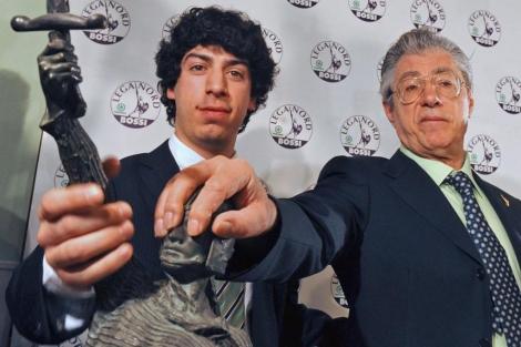 Umberto Bossi y su hijo Renzo, con la estatua símbolo de la Liga Norte en Milán.   Afp