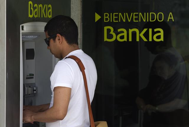 Un hombre saca dinero de un cajero de Bankia. | Reuters