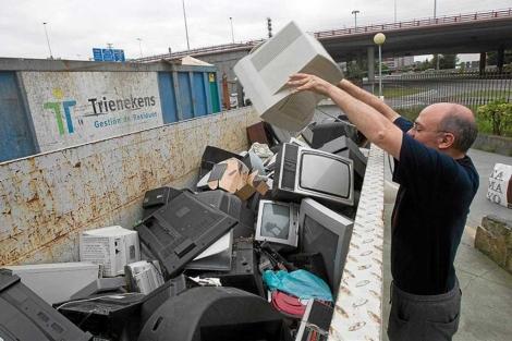Un hombre deposita un televisor en un punto limpio.   Mitxi