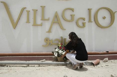Una mujer coloca flores en el centro comercial Villaggio, en Doha.   Reuters
