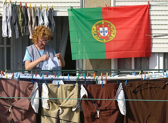 Una mujer tiende ropa con la bandera de Portugal colgada en su balcón. | AP