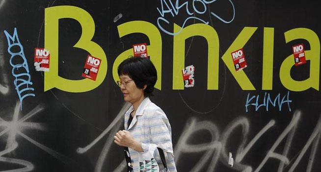 Una mujer pasa junto a una sucursal de Bankia en Madrid. | Reuters