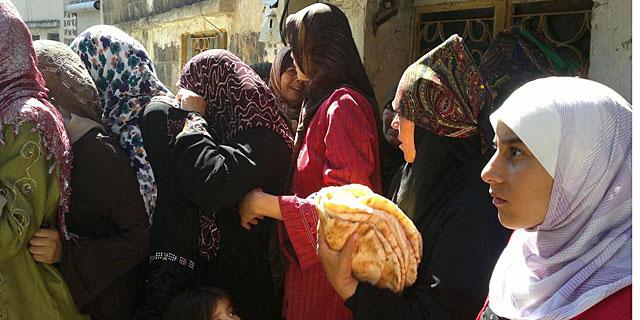 Mujeres hacen cola para obtener pan en Homs. | Afp