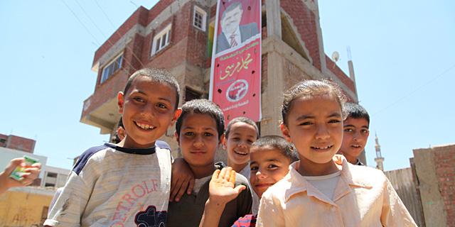 Varios niños delante del cartel que cuelga de la vivienda familiar de Mursi en su pueblo natal. | F. C