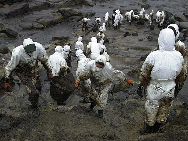 Voluntarios recogiendo chapapote de una playa gallega. | Lavandeira Jr/Efe