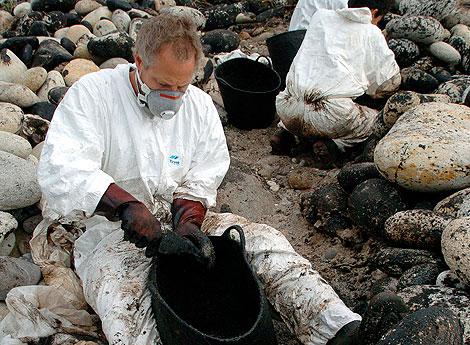 Un voluntario recoge chapapote de la costa en 2004, dos años después de la catástrofe. | Efe