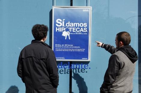 Un cartel publicitario sobre hipotecas de un banco llama la atención de dos jóvenes. | S. González
