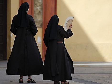 Dos monjas se abanican por el fuerte calor en Málaga. | Jorge Zapata/Efe