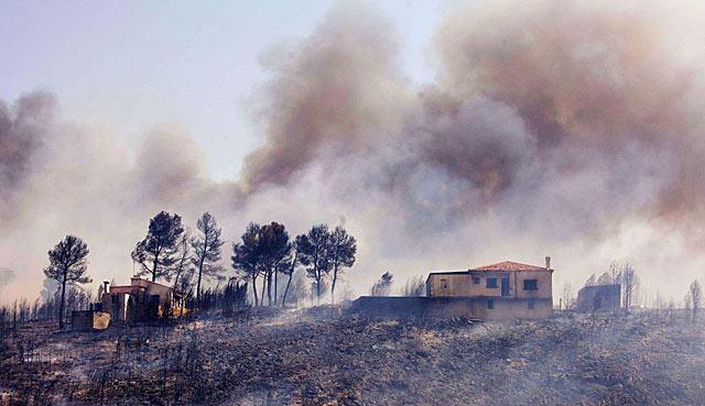 Una vivienda rodeada por el humo y el fuego | Afp