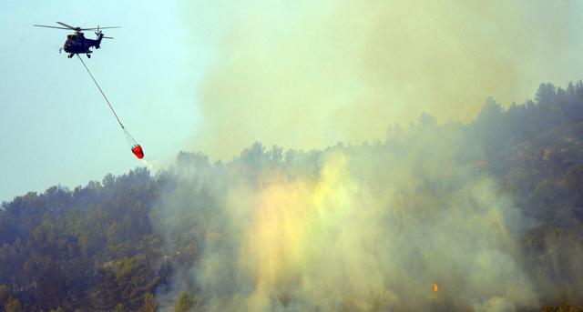 Un helicóptero trabaja en las tareas de extinción del fuego. | Jose Jordán