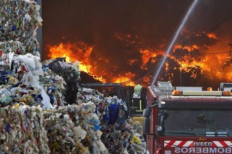 Los bomberos tratan de sofocar el incendio en la nave de Alcalá.   Efe