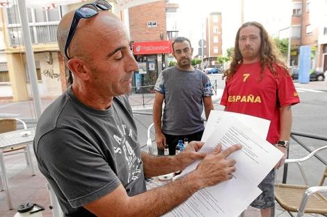 Daniel muestra el contrato de trabajo, junto a sus dos compañeros. | J. M. Lostau