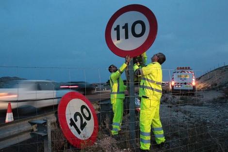 Operarios cambiando las señales de tráfico de 120 km/h a 110 km/h.   Ernesto Caparros
