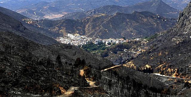 Imagen del pueblo de Dos aguas, rodeado por el monte quemado. | Foto: Efe