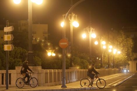 Dos ciclistas circulan por el centro de Valencia, iluminado por las farolas. | Vicent Bosch