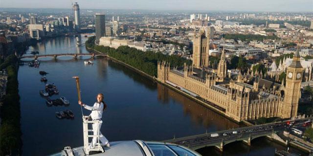 La atleta Amelia Hempleman-Adams, con la antorcha olímpica sobre la cápsula del 'London Eye'.   Reuters