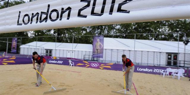 Voluntarios olímpicos preraran la arena de la pista de vóley-playa en Londres. | Efe