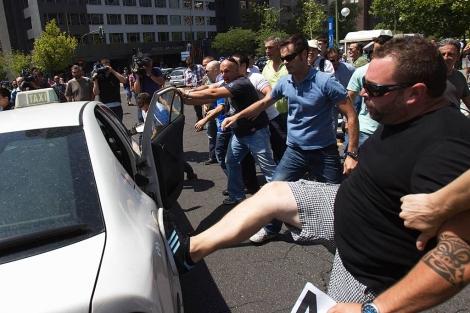 Taxistas golpean otro taxi durante su protesta.   Reuters