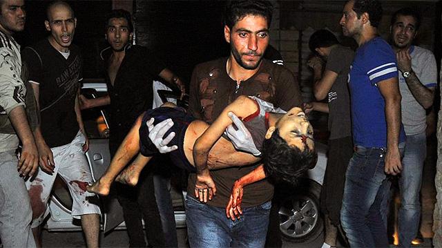 Un hombre traslada a un niño herido en Alepo.   EL MUNDO
