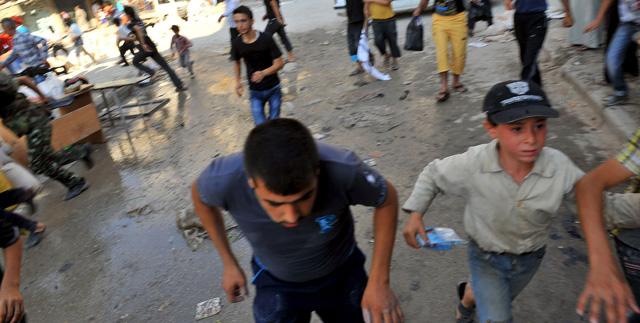 Civiles buscan un refugio para protegerse de los bombardeos en Alepo. | Afp