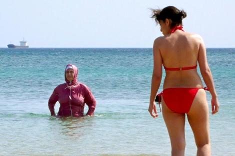 Una mujer turca y una turista en la playa Ayazma de la isla Bozcaada, en Turquía. | Efe