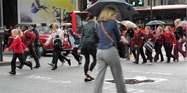 Varios peatones, entre ellos muchos niños de colegio, corren para cruzar una calle en Londres. | C. F.