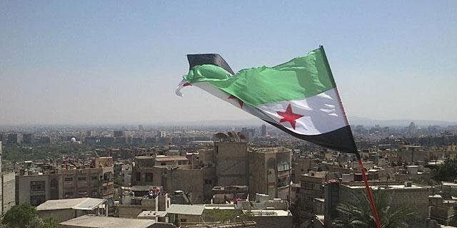 Una bandera rebelde siria ondea en el barrio de Ruknudin (Damasco). | Reuters