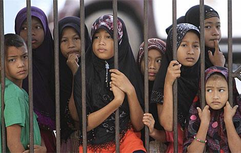 Niños en el exterior de su colegio, incendiado en Pattani. | Reuters