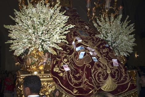 El manto de la Virgen con los billetes prendidos. | Efe