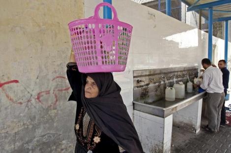 Una mujer palestina transporta botellas de agua.   Reuters