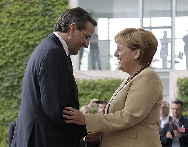 Antonis Samaras, primer ministro griego, saluda a Angela Merkel, canciller alemana, antes del inicio de la reunión, en Berlín. | Reuters