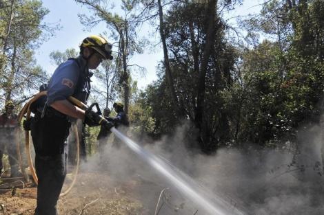 Un bombero remoja la zona afectada por el fuego. | Efe