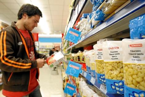 Un joven examina un paquete de pasta de marca blanca en un supermercado. | Foto: E. M.