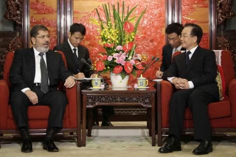 El presidente egipcio Mohamed Mursi habla con el primer ministro chino Wen Jiabao. | Reuters
