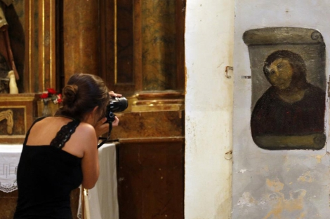 Una mujer fotografía la versión 'restaurada' del Ecce Homo. | AFP