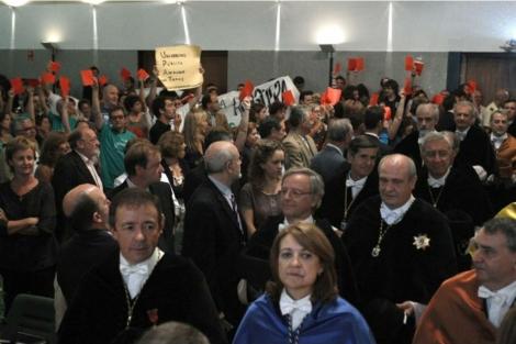 Los manifestantes sacan cartulinas rojas durante el acto. | EFE