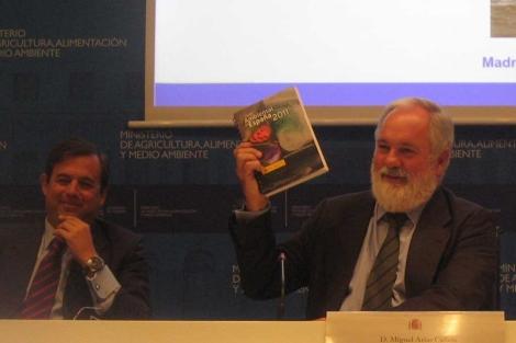 El secretario de Estado de Medio Ambiente, Federico Ramos de Armas (i) y el ministro Arias Cañete, con un ejemplar del 'Perfil Ambiental de España 2011'.| MAGRAMA