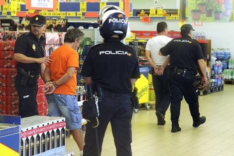 Dos de los manifestantes salen del supermercado detenidos por la Policía. | Efe